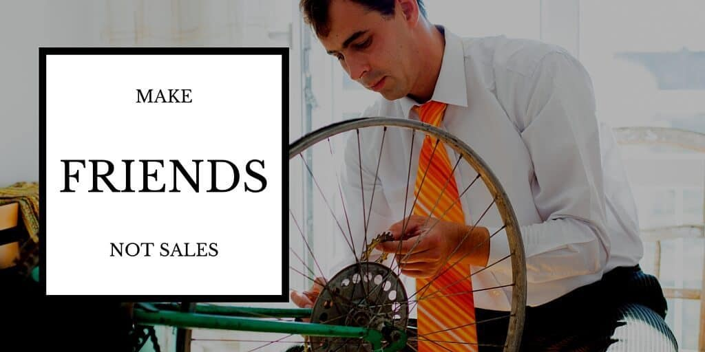 Build Lasting Client Relationships: Make Friends Not Sales. Picture: Business man in suit with jacket off fixing his bicycle tire.