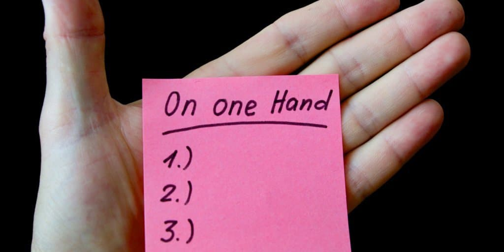 Hand with a sticky note list on it.