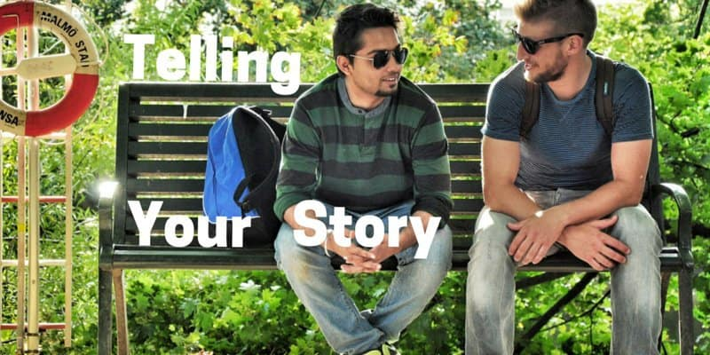 Two young men sitting on a park bench talking to each other, telling a story with graphics.